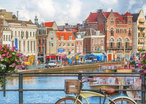bicycles on a bridge over a canal with colorful buildings