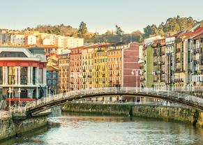 the ria del bilbao running through the city surrounded by colorful buildings