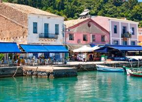 colorful boats and shops line the pier in katakolon, greece