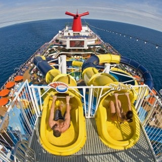 Man and woman preparing to ride water slide overlooking entire ship deck out at sea