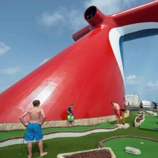 A group of boys play mini-golf next to the Carnival ship funnel