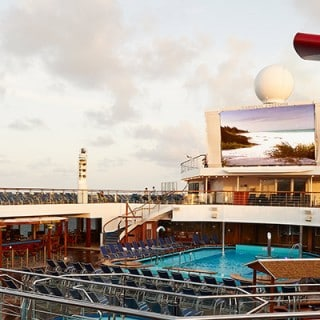 A side view of the ship's deck: pool, beach chairs, lights, TV screen and funnel
