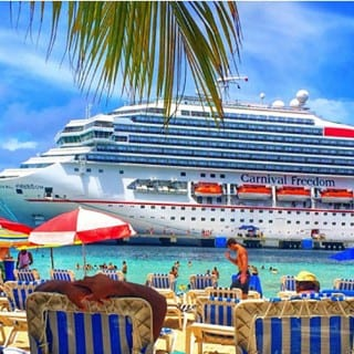 People enjoying beach chairs, umbrellas and swimming looking onto a docked carnival freedom