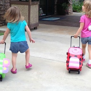 Two little girls walk into a building pulling their insect-themed luggage