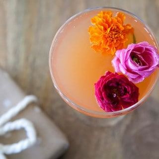looking into a glass filled with an orange cocktail and three small flower garnishes