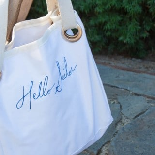 "Canvas handbag with text ""hello sailor"" draped over a chair"