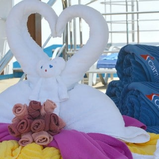 White towels formed into swans and a bear next to blue carnival-branded towels on ship