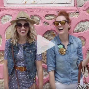 two girls with glasses post against a pink stone wall laughing, link to Youtube video