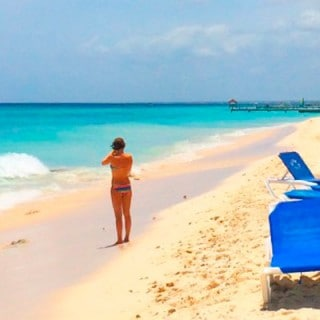 Woman wearing bikini stands at a beach next to a cluster of chairs in the caribbean
