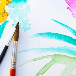 Two paint brushes sit on a pad of paper painted on with a floral images