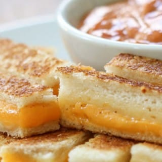 Plate of long grilled cheese slices and bowl of tomato soup