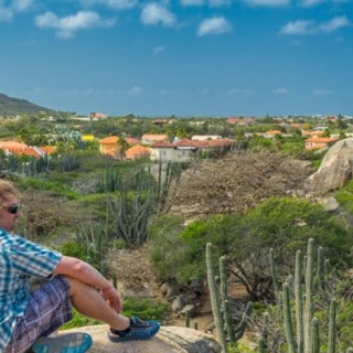 Man sitting on cliff looking over village with vulcano
