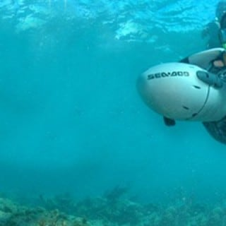 Two people underwater with handheld propellers in the caribbean
