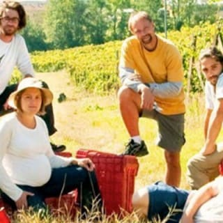 Group of men and women sit in a vineyard hill with baskets