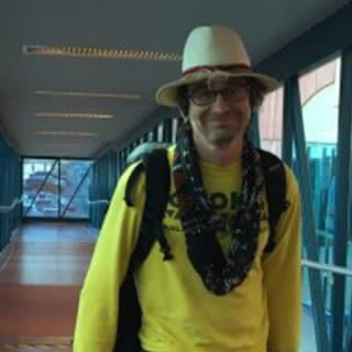 Man walking down a window-lined hallway onto carnival ship