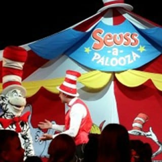 Costumed Cat in the Hat on stage with two performers on carnival ship