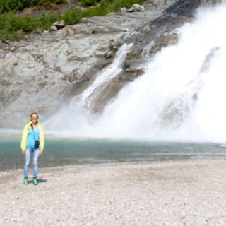 Woman standing next to large waterfall in Alaska