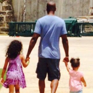 Man holding two girls hands, walking down side walk
