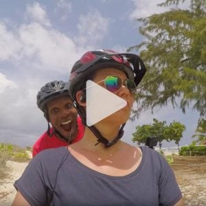 Man and woman biking with helmets on with beach in the background, link to Youtube video