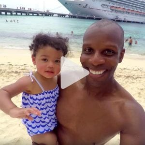 Man holding his daughter taking a selfie on the beach in front of Carnival cruise ship, link to Youtube video