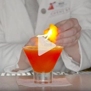 a cocktail with a flaming piece of fruit being added to it by a Carnival mixologist, link to Youtube video