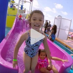 little girl smiles as she comes off of the water slide on Carnival cruise, link to YouTube video