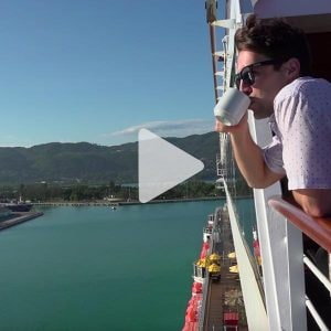 Man stands on deck of ship drinking a cup of coffee looking at the water, link to Youtube video