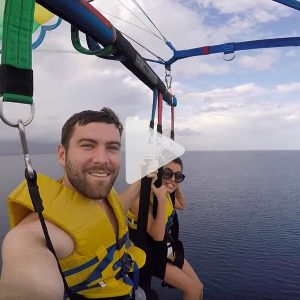 Man and woman floating over the ocean parasailing on a Carnival excursion, link to Youtube video