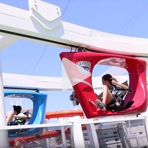 two children ride on blue and red sky rides on a Carnival ship, link to Youtube video