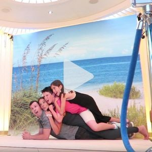 a family of four poses in a pig pile style professional photo with a beach backdrop on a Carnival ship, link to Youtube video