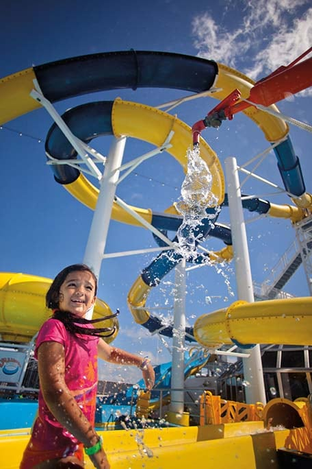 little girl standing underneath the waterworks waterslide