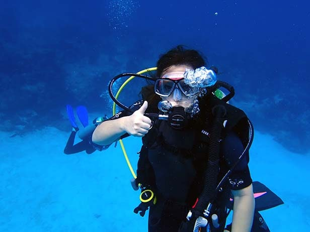 woman giving a thumbs up while scuba diving