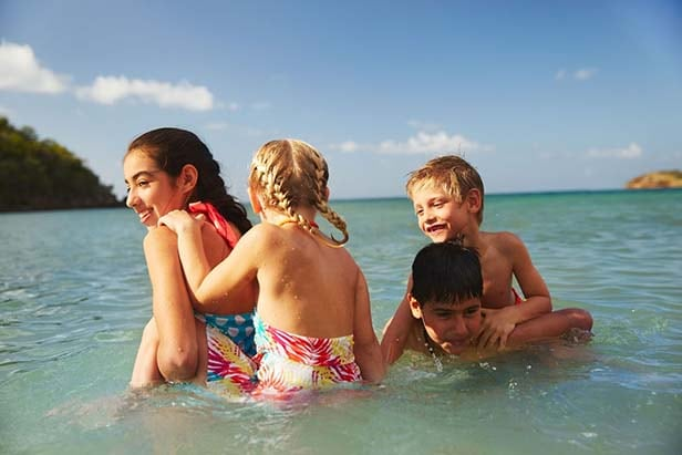 group of kids playing in the water at a caribbean beach