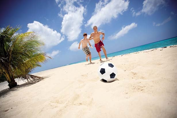 two boys playing soccer on a caribbean beach