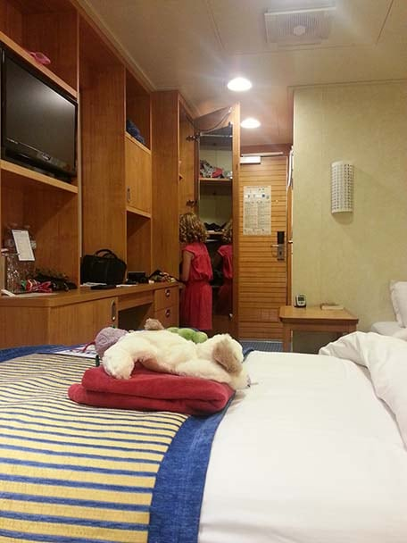 woman checking out the closet in her carnival stateroom