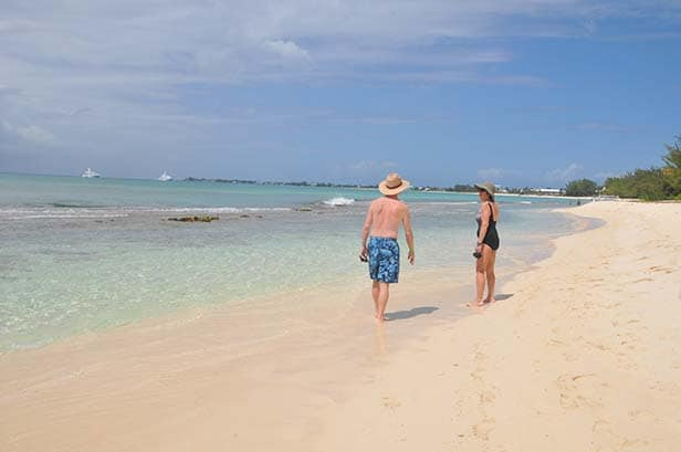 two people walking along seven mile beach in grand cayman