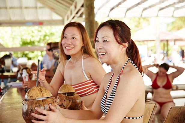 two women enjoying fresh coconut drinks in princess cays