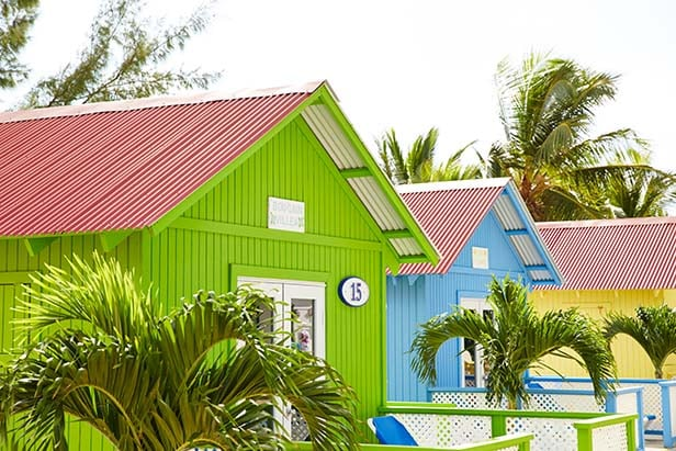 pastel colored private beach bungalows in princess cays