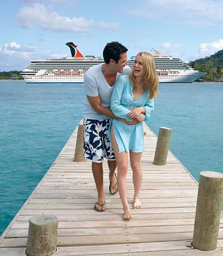 a couple holding each other in front of a carnival ship