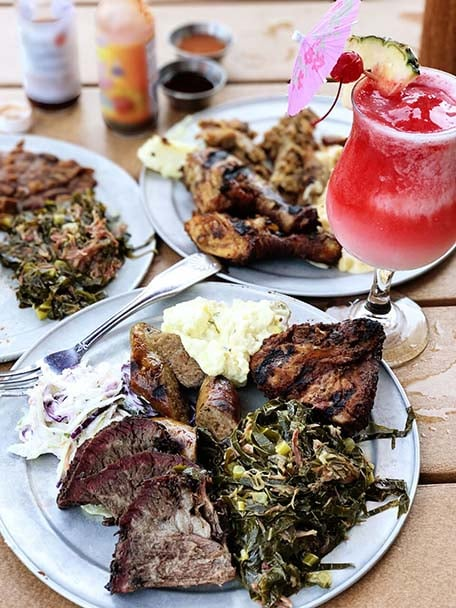 Three BBQ plates typical of the South Caribbean and red cocktail