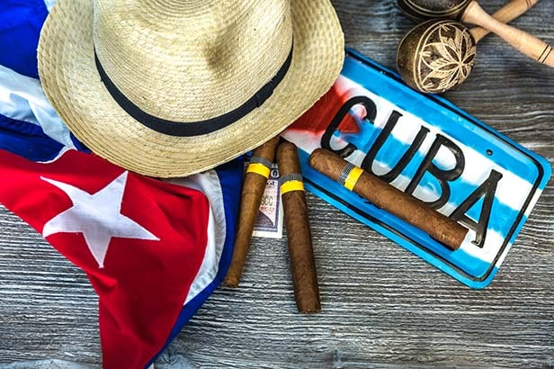 Cuban cigars next to a hat and cuba license plate