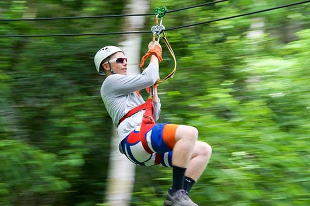 man ziplining in belize