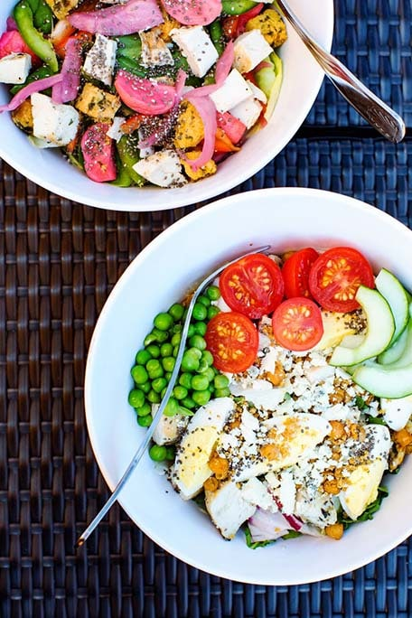 Two salads in large white bowls on outdoor furniture