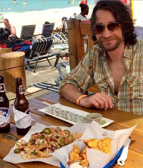 Randy sitting at a table with sushi, chips and nachos at West End Beach, Roatan Honduras