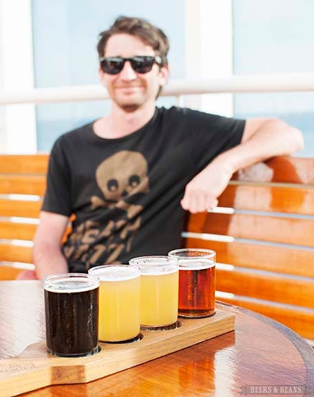 Four beer tastings sitting on a wooden holder with Randy in the background wearing sunglasses and a black shirt