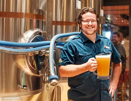 Brewmaster Colin Presby holding a pitcher of IPA in front of beer tanks on Carnival Vista