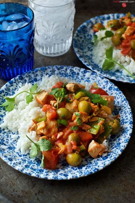 Dominican Pollo Guisado dish with blue and clear cups on water to the side