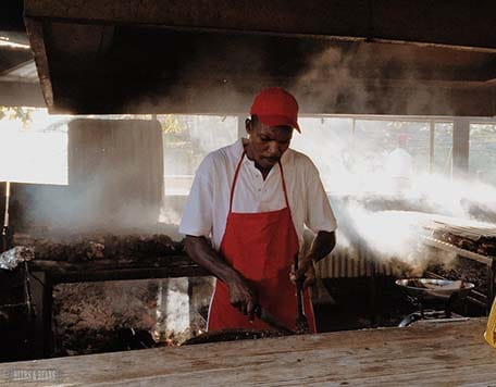 Man wearing red hat and apron while cooking jerk chicken in Montego Bay