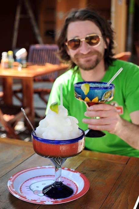 Large frozen margarita sitting on a wooden table with Randy holding up a margarita in the background