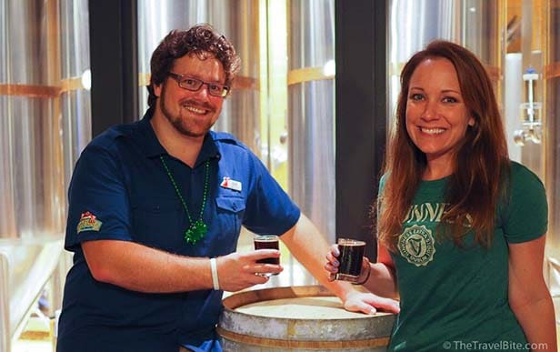 Rachelle with carnival Brewmaster at RedFrog Brewery smiling and each holding a beer